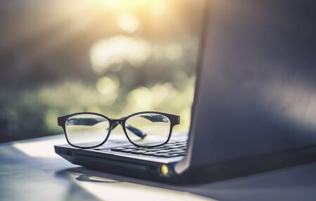 Photo for Glasses placed on the laptop in the library. - Royalty Free Image