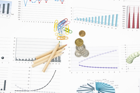 Business still-life of pencil, charts, coins, paperclip