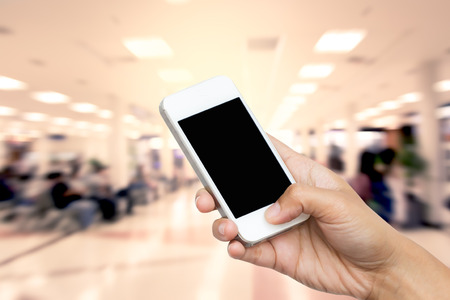 woman hand hold smart phone, tablet,cellphone on blurred of lifestyle at waiting chair zone in airport background