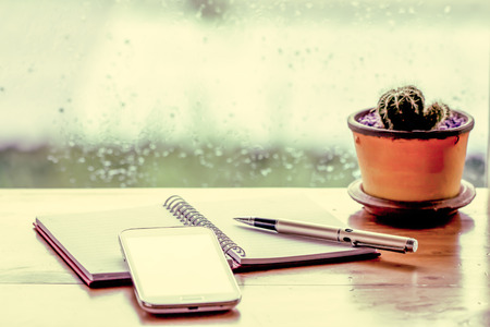 Phone with pen on notebook  on  rainy day window background  in vintage color tone