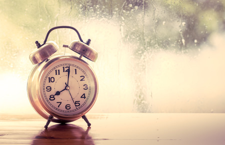 retro alarm clock on wooden table on rainy day window
