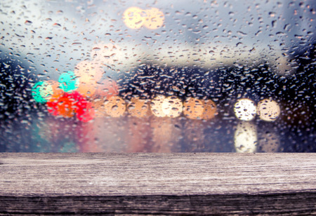 wooden table with blur traffic view through a car windscreen covered in rain for backgroundの写真素材