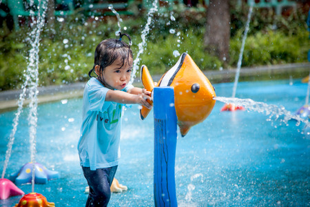 Photo pour Child little girl having fun to play with water in park fountain in summer time - image libre de droit