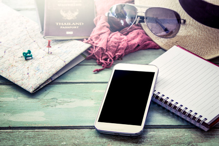 Photo for Preparation for travel, cellphone, sunglasses ,passport, road map,hat and notebook on wooden table in vintage filter - Royalty Free Image