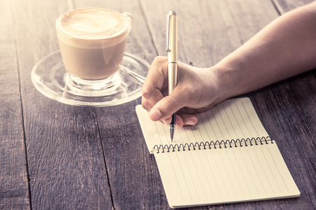 Photo pour Woman hand writing on notebook over wooden table with coffee cup in vintage color filter - image libre de droit