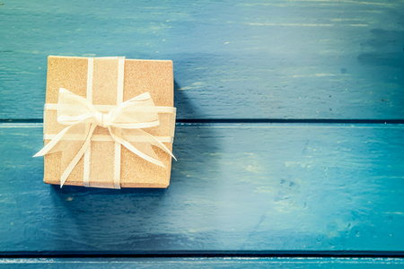 Gift box on blue wooden table,vintage filter