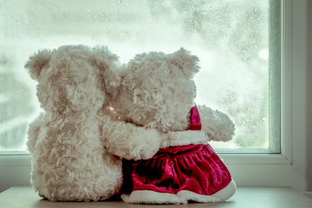 Couple teddy bears in love's embrace sitting in front of a rainy day window,vintage filter