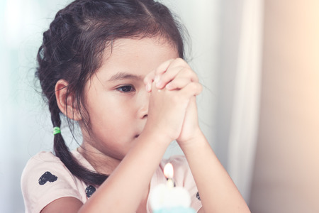 Cute asian little child girl make folded hand to wish the good things for her birthday in party in vintage color tone