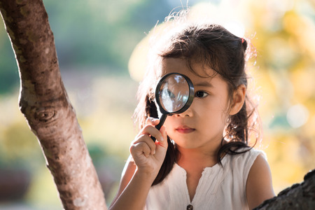 Asian little child girl looking through a magnifying glass on the tree in the park