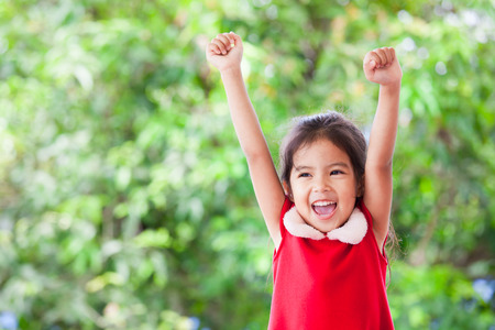 Foto de Happy asian child girl in christmas dress raising her hands and shouting with cheerful on green nature background - Imagen libre de derechos