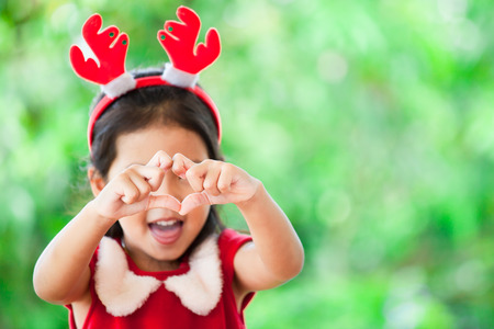 Photo pour Cute asian child girl in christmas dress making heart shape with hands on green nature background. Love and Christmas concept - image libre de droit