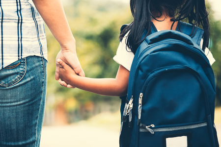 Photo pour Back to school. Cute asian pupil girl with backpack holding her mother hand and going to school in vintage color tone - image libre de droit