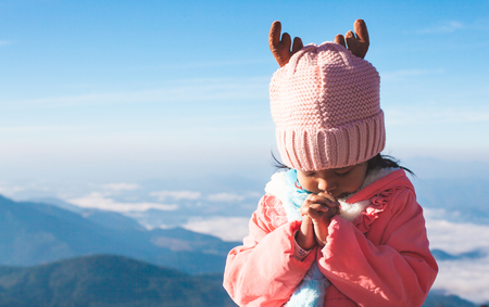 Photo for Cute asian child girl wearing sweater and warm hat making folded hands in prayer in beautiful mist and mountain background in winter - Royalty Free Image