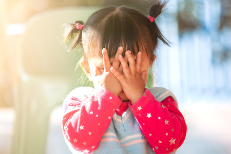 Photo pour Cute asian baby girl closing her face and playing peekaboo or hide and seek with fun - image libre de droit