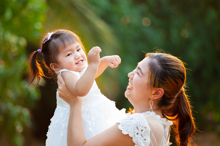 Photo pour Asian mother carrying her daughter up in the air and playing together in the park with fun and love - image libre de droit