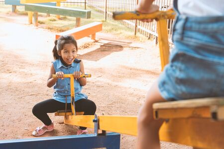 Foto de Two cute asian child girls playing seesaw together in the playground with fun - Imagen libre de derechos