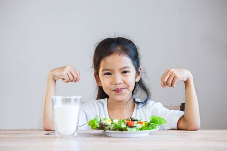 Photo pour Cute asian child girl eating healthy vegetables and milk for her meal - image libre de droit
