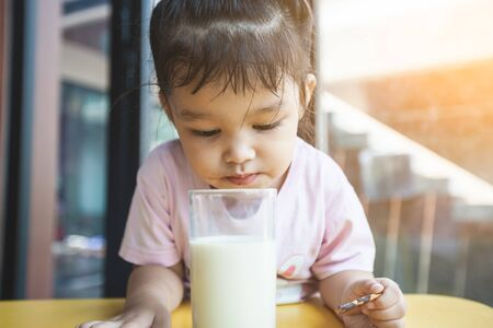 Photo pour Cute asian little child girl drinking milk and eating snack in breakfast time - image libre de droit