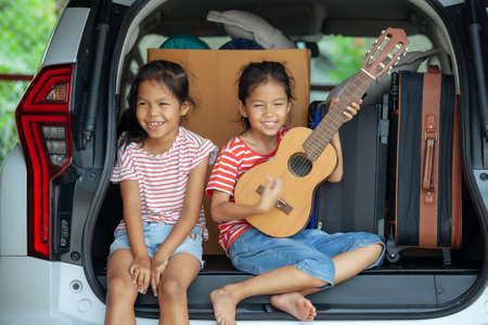 Photo pour Happy asian child girl playing guitar and singing a song with her sister in a car trunk in family trip. - image libre de droit