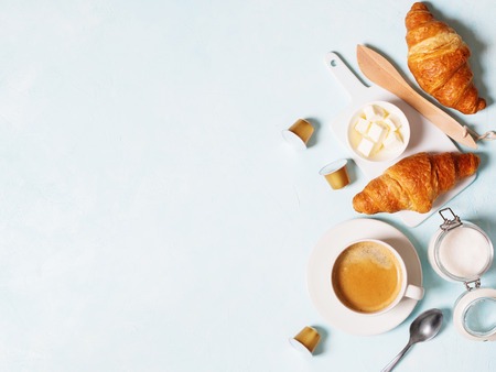 Photo pour Breakfast concept. Coffee espresso in white cup, coffee beans, capsules, croissants, butter on a blue pastel background with space for text. Flat lay. - image libre de droit