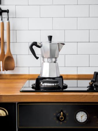Foto de Closeup of Moka coffee pot on a gas stove against a wall with white tiles in kitchen with free space for text. scandinavian design interior. - Imagen libre de derechos