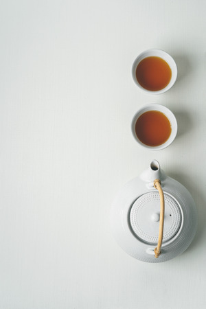 Foto de Asian minimalistic tea concept, two white cups of tea and teapot view from above, space for a text on white fabric background. - Imagen libre de derechos
