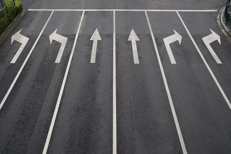 Arrow signs as road markings on a street with six lanes