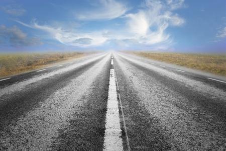 Long straight asphalt road and blue cloudy summer sky