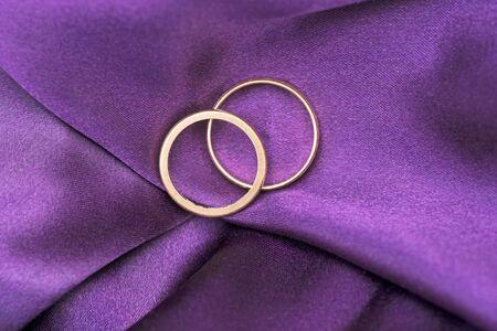 Photo pour Two wedding rings on purple silk - image libre de droit