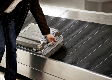 Man picking up metal suitcase from conveyor belt at airport