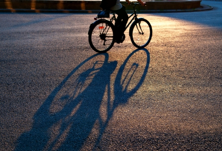 Shadow of cyclist on city street in evening light  Focus on shadow