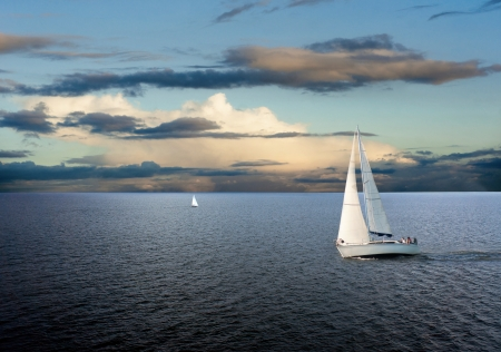 Sail boats on sea with cloudy sky