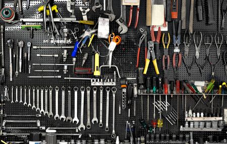 Black wall with many tools in workshop