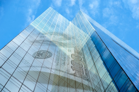 Office building with hundred dollar bill on blue sky with fluffy clouds