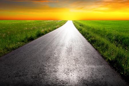 country road leading into orange sunrise