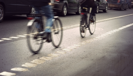 Cyclists in blurred motion in busy street on gloomy rainy day
