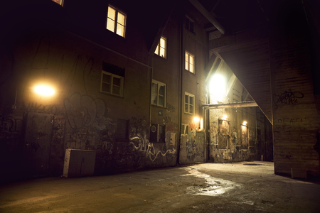 spooky messy dark alley with graffiti at night