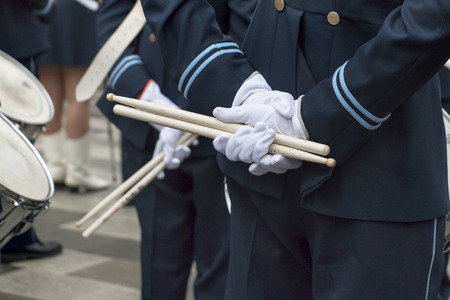 Hands of men in marching band with drumsticks