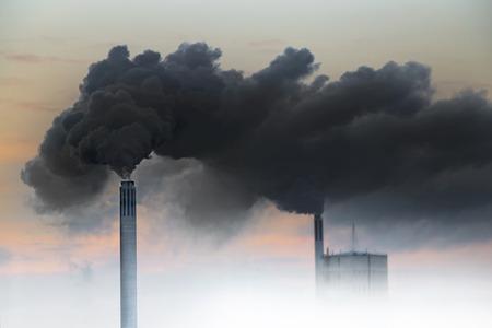 Photo pour Dark smoke from chimneys of power plant on orange sky - image libre de droit