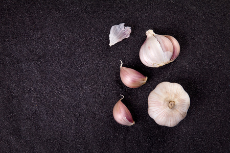 still life arrangement of Three whole garlic bulbs grouped on black stone plate