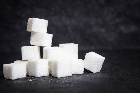 cloose up the white sugar cubes on black stone plate background