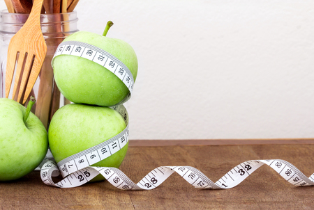 the green apple with Measuring tape on wooden background in concept of healthy and diet