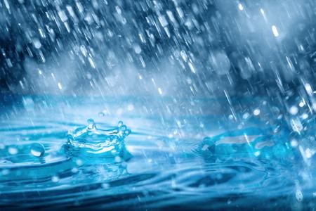 Foto de Blue Drops falling down  of heavy rain weather  on water - Imagen libre de derechos