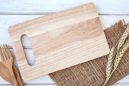 Foto de  chopping board and tablecloth with wooden fork and spoon on white table , recipes food  for healthy habits shot note background concept - Imagen libre de derechos
