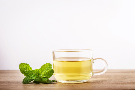 Foto per Close up glass cup of mint tea with green fresh peppermint leaves , relaxation and healthy drink - Immagine Royalty Free