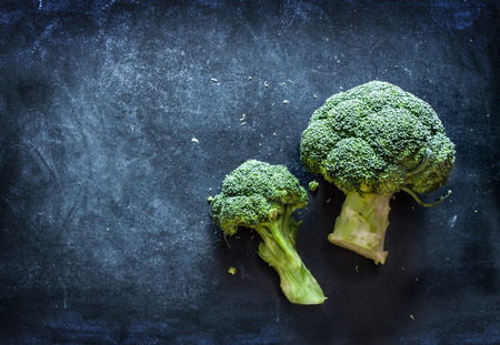Raw broccoli on black chalkboard. Background with free text space.