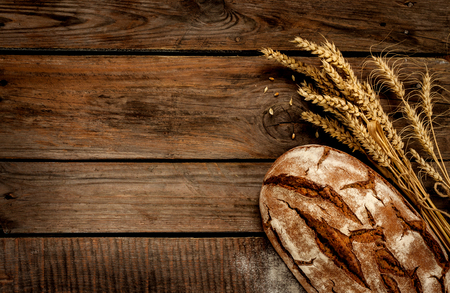 Photo for Rustic bread and wheat on an old vintage planked wood table. Dark moody background with free text space. - Royalty Free Image
