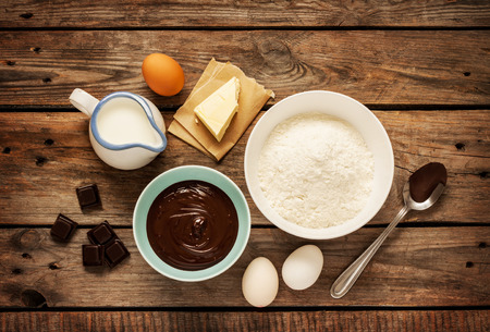 Baking chocolate cake in rural or rustic kitchen. Dough recipe ingredients (eggs, flour, milk, butter) on vintage wood table from above.
