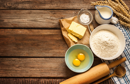 Baking cake in rural kitchen - dough recipe ingredients (eggs, flour, milk, butter, sugar) and rolling pin on vintage wood table from above.