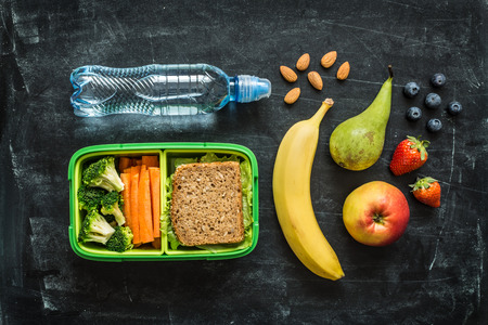 Photo for School lunch box with sandwich, vegetables, water, almonds and fruits on black chalkboard background. Healthy eating habits concept. Flat lay composition (from above, top view). - Royalty Free Image